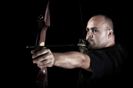 Archer in black on black background aiming with bow and arrow, with focus on bow.  photo