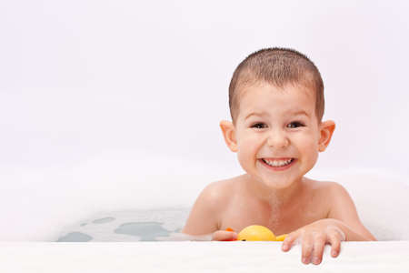 child bath: Boy playing in the water with toy Stock Photo