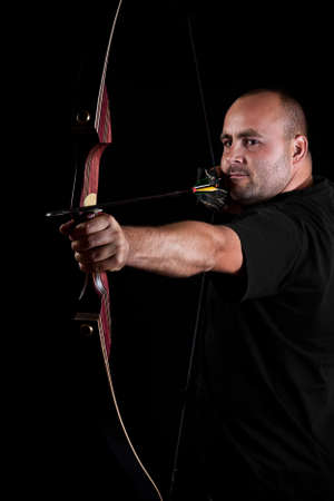Archer in black on black background aiming with bow and arrow, with focus on eyes.  photo