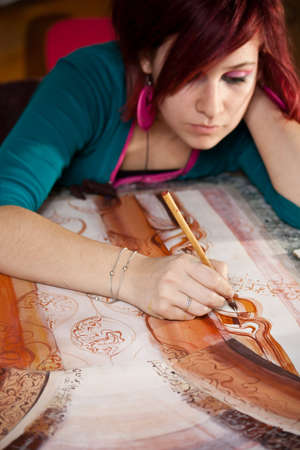 hand painting: Young female artist painting in studio  Stock Photo