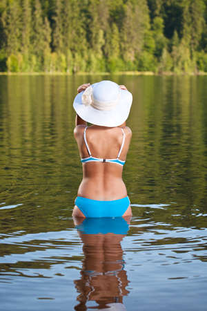 beautiful girl relaxing in bikini wearing in water an elegant summer hat  photo