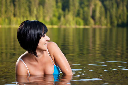 beautiful girl relaxing in bikini wearing in lake water photo