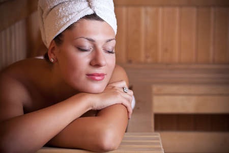 sauna: Beautiful young woman relaxing in the sauna