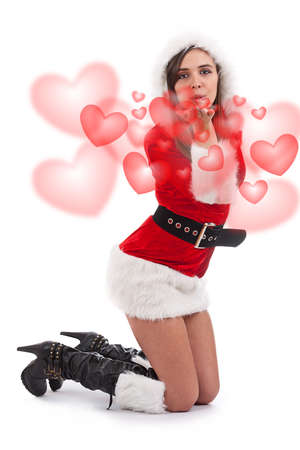 Beautiful and sexy woman wearing santa clause costume sending hearts photo