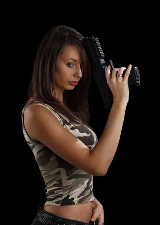 radical love: Shot of a beautiful girl holding gun, isolated on black bckground