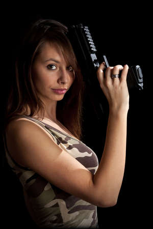 Shot of a beautiful girl holding gun, isolated on black bckground photo
