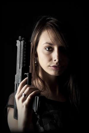 mujer con pistola: Disparo de un arma chica hermosa celebración, aislado en fondo negro Foto de archivo