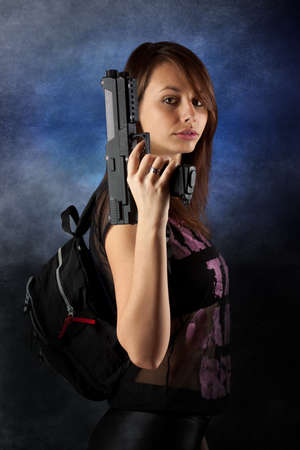 Shot of a sexy freestyle woman posing with pistol