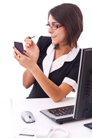 Beautiful businesswoman applying lipstick using lip concealer brush in the office  photo