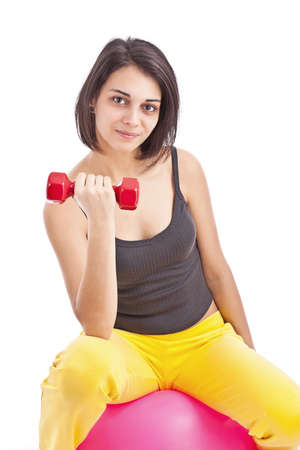 Portrait of a fit woman working out with dumbbells and a ball against a white background  photo