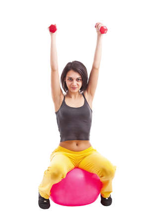 Fit woman working out with dumbbells and a ball against a white background  photo