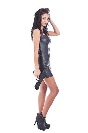 mujer con pistola: Sexy chica en cuero negro con arma de fuego, aislado en blanco Foto de archivo