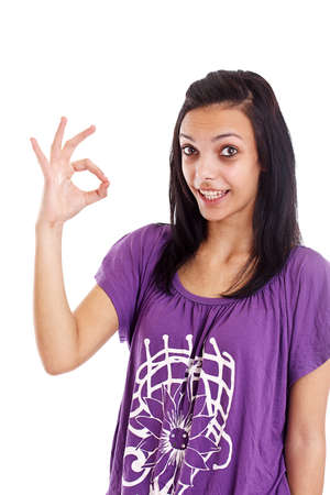 Portrait of beautiful young woman gesturing a okay sign on white background  photo