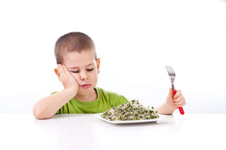 to sulk: Boy refuses to eating healthy food, isolated on white