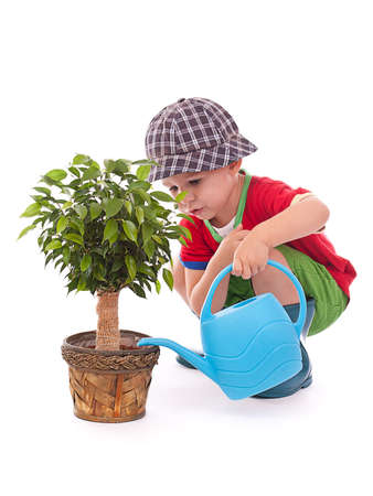 a boy with a watering-can is giving the flowers some water