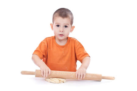 Little boy in the kitchen using rolling pin to prepare the dough for cookies photo