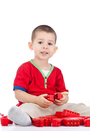 little boy playing with red blocks