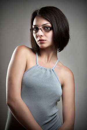 woman wearing glasses: Young woman wearing glasses, gray background