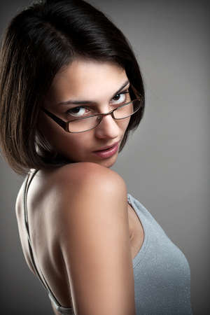 Young woman wearing glasses, gray background photo