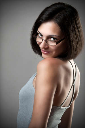 cordial: Happy young woman wearing eyeglasses looking to the camera on grey background Stock Photo