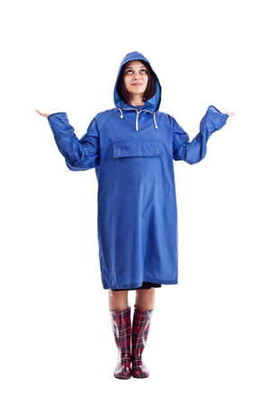 Young woman, isolated against a white background, wears a blue raincoat, waiting for it to rain.  Stock Photo