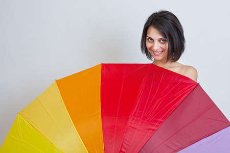 Young beautiful brunette woman hiding over colorful umbrella photo