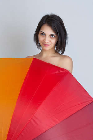 Young beautiful brunette female hiding over colorful umbrella photo