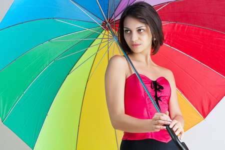 Portrait of beautiful brunette female standing under umbrella photo