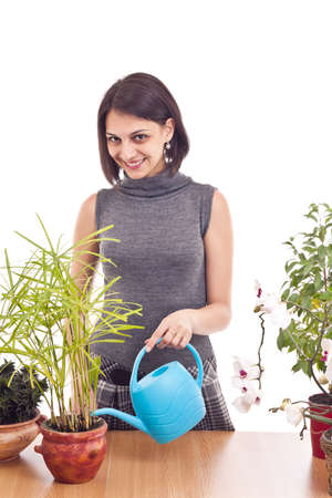 irrigate: Beautiful happy young woman irrigate plants in flowerpots isolated on white  Stock Photo