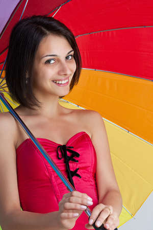 Woman standing with rainbow umbrella photo