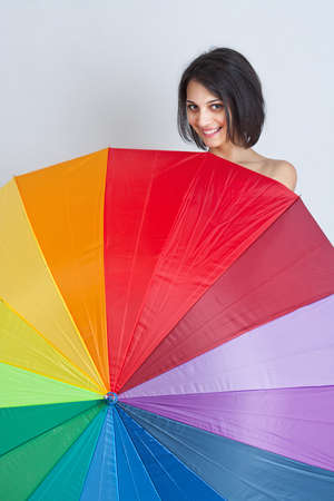 Young beautiful brunette female hiding over rainbow umbrella photo