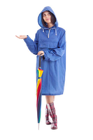 slicker: Pretty young girl in a raincoat and umbrella checks to see if it is raining