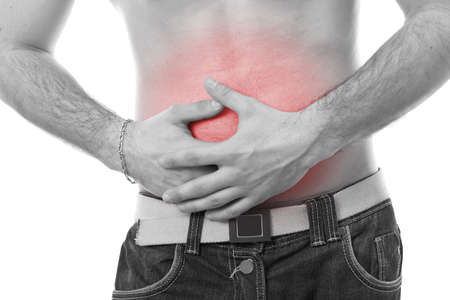 tummy: Young man having stomach pain, in white background, monochrome photo with red as a symbol for the hardening  Stock Photo