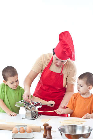 Two children and their mother with a preparation pasta together in the kitchen  photo