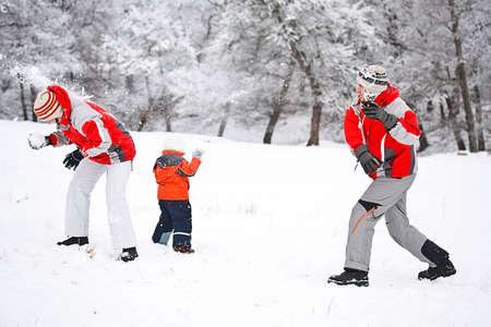bolas de nieve: Familia joven lanzando bolas de nieve en las vacaciones de invierno