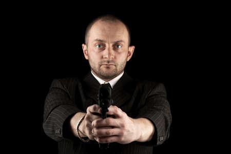 Gunman ready to shoot, isolated on black photo