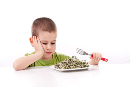 Boy refuses to eating healthy food, isolated on white  Stock Photo