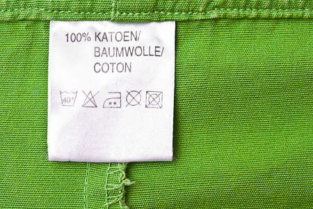 or instruction: Clothing label washing instruction tag on green t-shirt