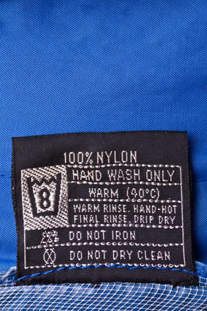 Clothing label washing instruction tag on blue raincoat  photo