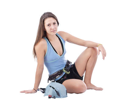 limber: Attractive girl in climbing equipment limber up in white background