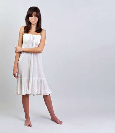 Girl in summer dress on grey background  photo