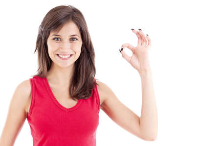 Beautiful girl showing OK sign and smiling, over white background