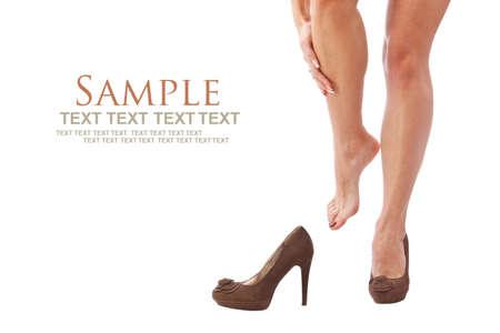 pies sexis: mujer frotando sus piernas sobre el fondo blanco Foto de archivo