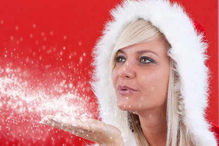 Attracive girl in santa cloth blowing snow from hands.  photo
