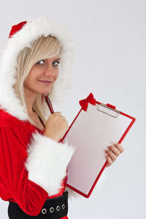 Beautiful christmas woman in santa wear holding empty board  photo