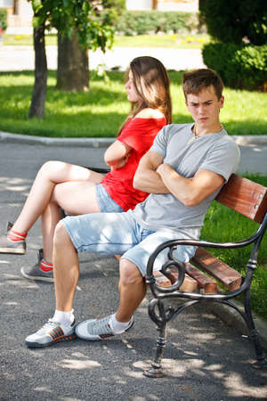 Young couple sitting on bench in park, not talking each other  photo