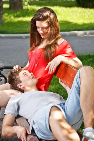 Teen boyfriend lying on his girlfriends lap  photo