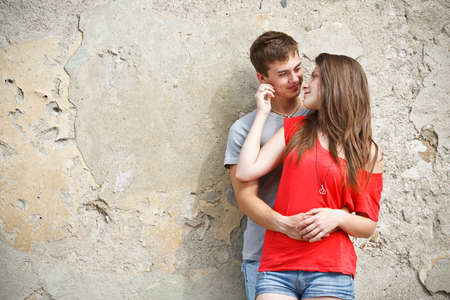 Young couple is standing grunge wall and hugging