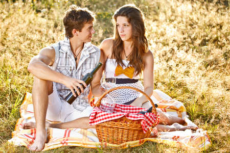 Young couple celebrating with wine at picnic  photo