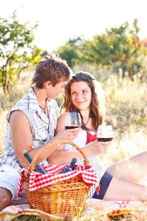 Young happy couple celebrating with wine at picnic  photo
